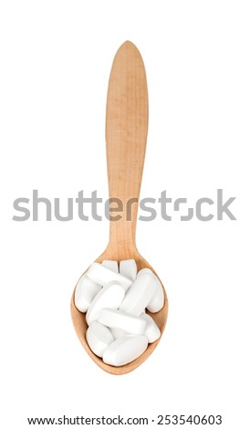 wooden spoon with pills isolated - stock photo