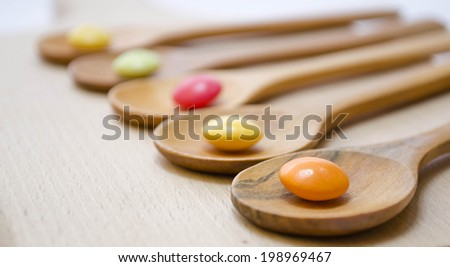 wooden spoon with pills on the background - stock photo