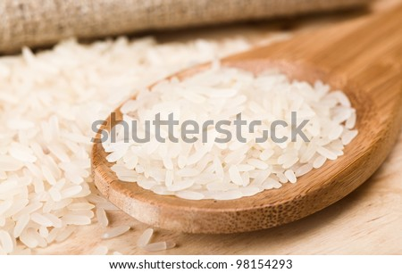 wooden spoon with raw rice - stock photo