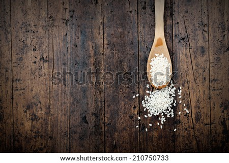 wooden spoon with rice beans on rustic background - stock photo