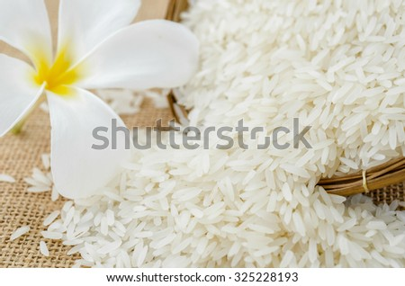 Wooden Spoon with rice jasmine and white flower - stock photo