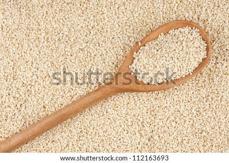Wooden spoon with sesame seeds, sesame lies against - stock photo