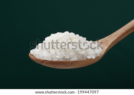 Wooden spoon with white rice - stock photo