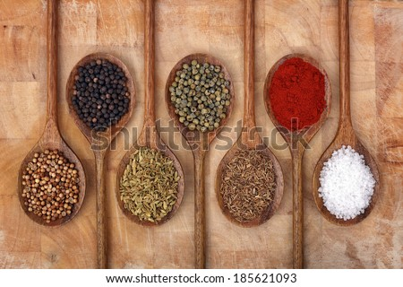 Wooden spoons full of aromatic herbs and spices on a wood cutting board - stock photo
