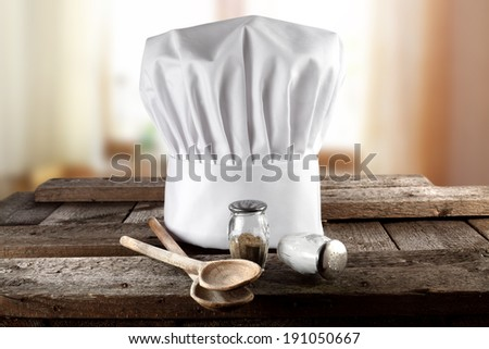 wooden spoons window in kitchen and cook hat  - stock photo