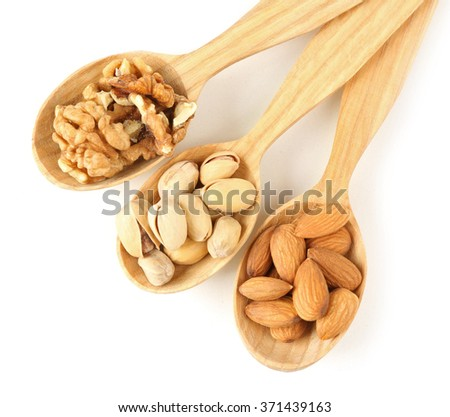 Wooden spoons with walnuts, pistachios and almonds, isolated on white - stock photo