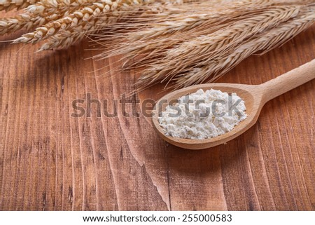 wooden sppon with flour and ears of wheat on vintage wooden board - stock photo