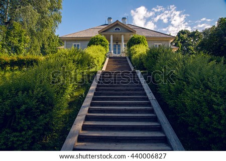 wooden staircase with a lift at the sides grow large green bushes and at the end of which stands the house of the Tree in summer day. - stock photo