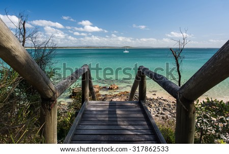 Wooden Stairs Leading to a Pristine Beach Paradise Overlooking a White Sail Boat and Mountains During a Beautiful Summer Day, Noosa National Park, Noosa Heads, Sunshine Coast, Queensland, Australia - stock photo