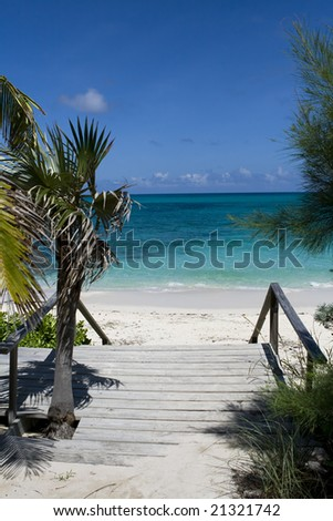 Wooden step entrance to a beautiful tropical beach. - stock photo