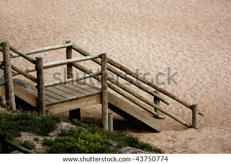 Wooden steps to the beach surrounded in sand and grass. - stock photo