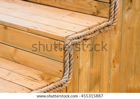 Wooden steps with rope decoration. Close up - stock photo
