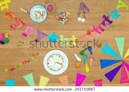 Wooden surface with an assorted array of birthday party items and objects, such as cake, candles, garlands, whistles, balloons and such, seen from above. A top view background for invitations - stock photo