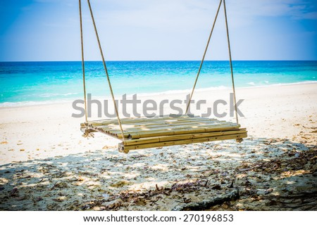 Wooden swing on beautiful white sand tropical beach, Thailand. - stock photo