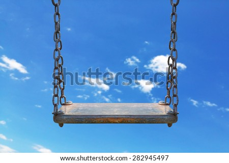 wooden swing with blue sky background - stock photo