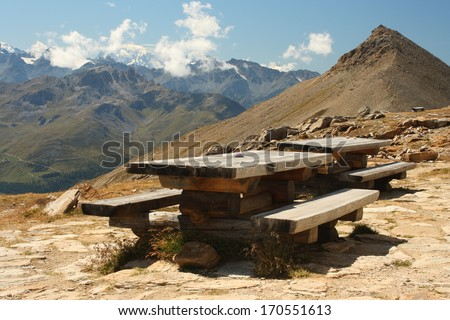 wooden table and benches in Swiss Alps - stock photo