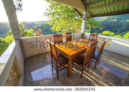 Wooden table and chair at balcony with natural sunlight and tropical view background - stock photo