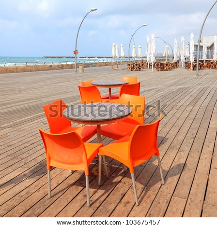 Wooden table and orange chairs on the wooden embankment of the seaside background - stock photo