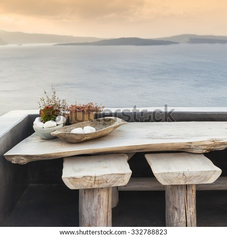 Wooden table and stools on a terrace in Santorini - stock photo