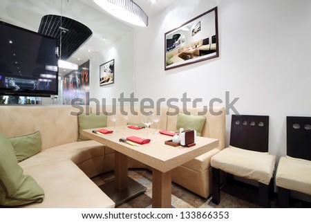 Wooden table, beige leather sofa and mirror in cozy Japanese restaurant. - stock photo