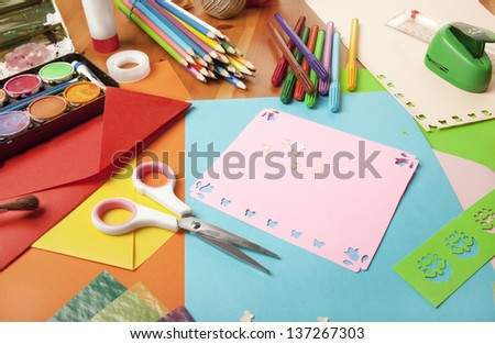 wooden table decoration itself to tinker around with scissors, pencils and drawing paper - stock photo
