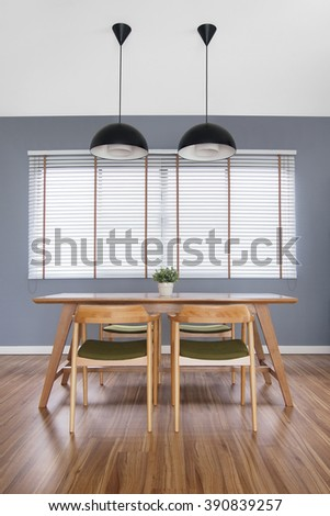 wooden table in cozy dining room with blinds window, decorate idea, dining chairs, empty table, loft style lamps, laminate floor, plant pot, grey concrete wall - stock photo