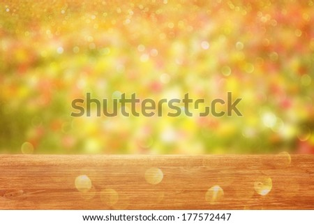 wooden table in front of field colorfull flowers boke light.  - stock photo