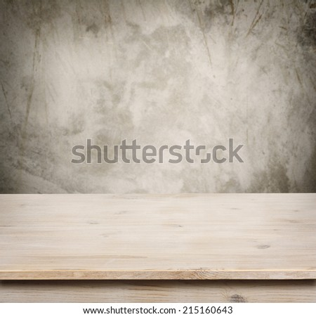 Wooden table on defocuced vintage wall background - stock photo