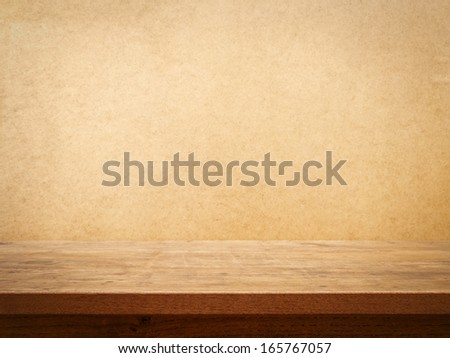 Wooden table on grunge wall background - stock photo