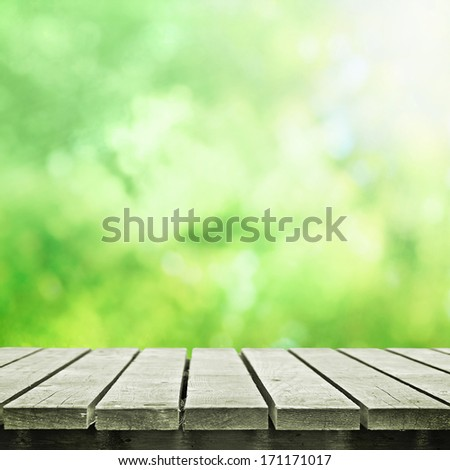 Wooden table on spring meadow - stock photo