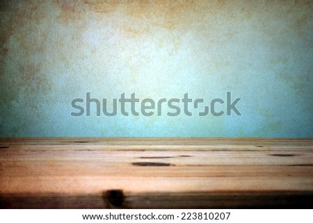 wooden table over wall grunge background - stock photo