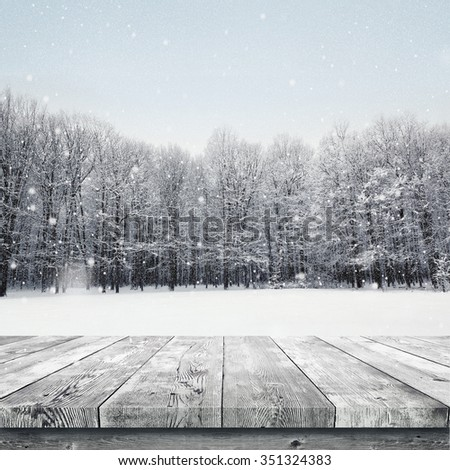 Wooden table over winter snow covered forest. Beauty nature background - stock photo