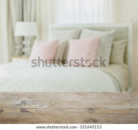 wooden table top with blur of luxury bedroom interior with pink pillows on bed - stock photo