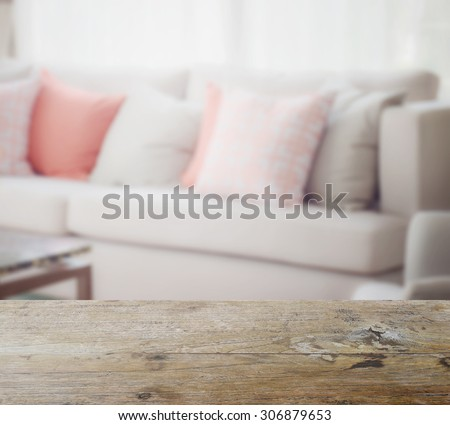 wooden table top with blur of orange and gray pillows setting on light gray in modern living room - stock photo