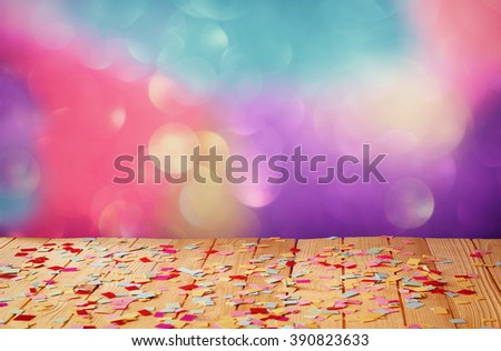 wooden table with colorful confetti. vintage filtered image  - stock photo