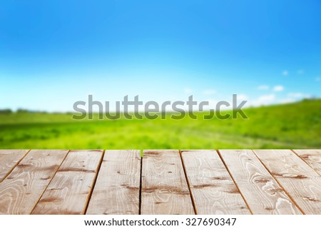 Wooden table with field background - stock photo