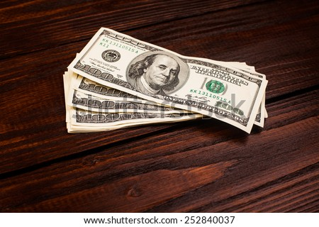 Wooden table with money american hundred dollar bills - stock photo