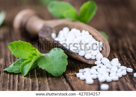 Wooden table with Stevia sweetener pills (selective focus; close-up shot) - stock photo