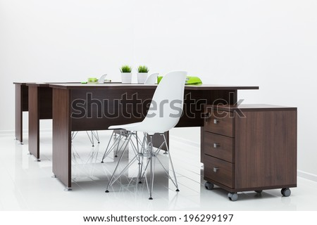 wooden tables and white plastic chairs in the office - stock photo