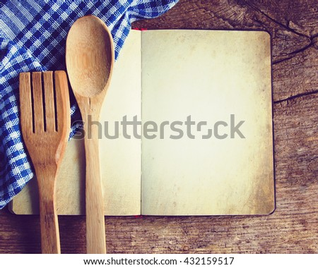 Wooden tableware and a notebook for recipes on the old board. Retro style. - stock photo