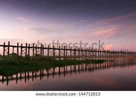 wooden teak U Bein bridge glowing at sunset near Amarapura, Burma - stock photo