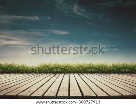 wooden terrace with fresh spring green grass and blue sky vintage style - stock photo
