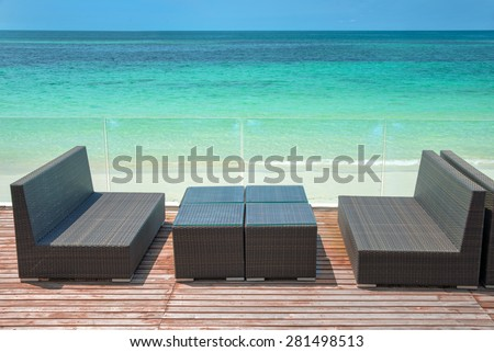 Wooden terrace with perfect sea view, lounge sofa and table - stock photo