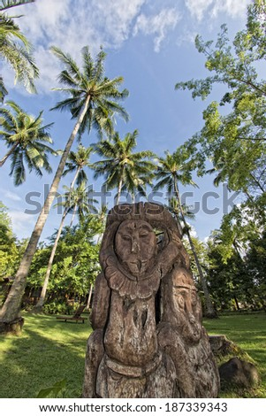 wooden tiki on tropical paradise beach with coconut trees - stock photo