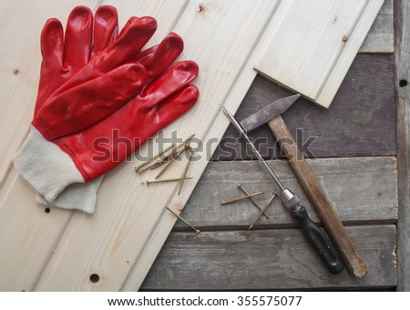 Wooden tile boards with instruments. Photo of a new wooden tile laying on the old tile with rubber gloves, hammer & screwdriver. - stock photo