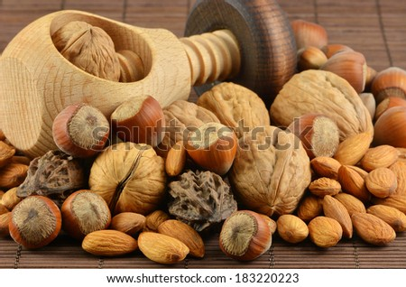 Wooden tool for crashing nuts with different  nuts on bamboo napkin - stock photo