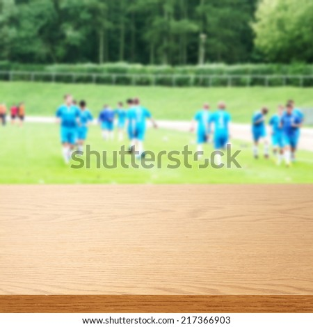 wooden top of yellow color and sport background with green grass  - stock photo