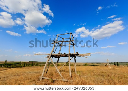 Wooden tower viewpoint in steppe under nice sky - stock photo