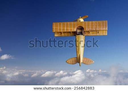 wooden toy airplane against blue sky and cloud - stock photo