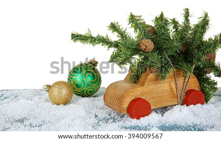 Wooden toy car with Christmas tree and baubles on a snowy table over white background - stock photo
